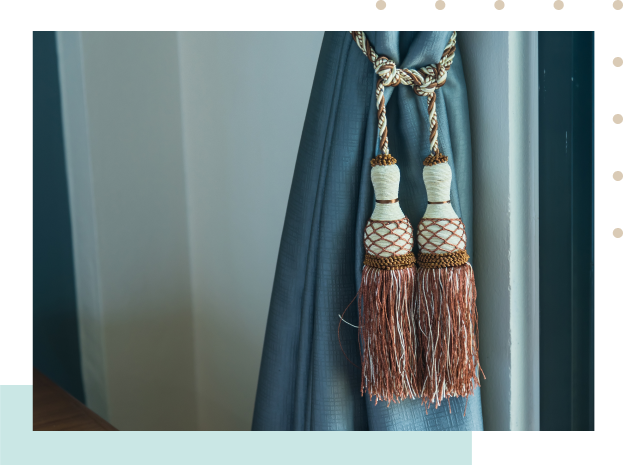teal curtain tied with white rope with rust details